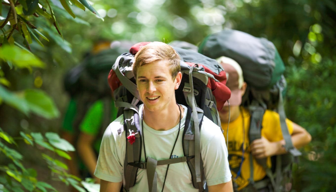 Male backpacking through forest