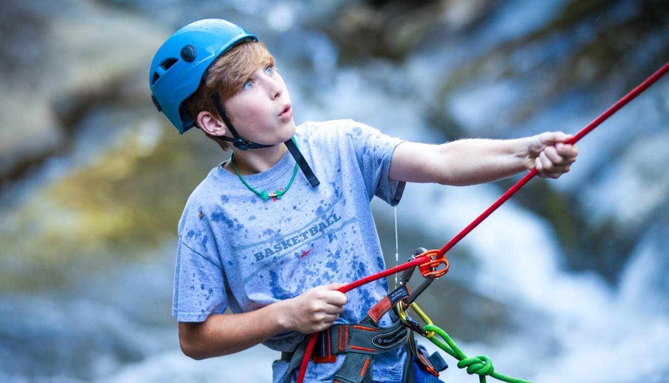 Young boy repelling at climbing