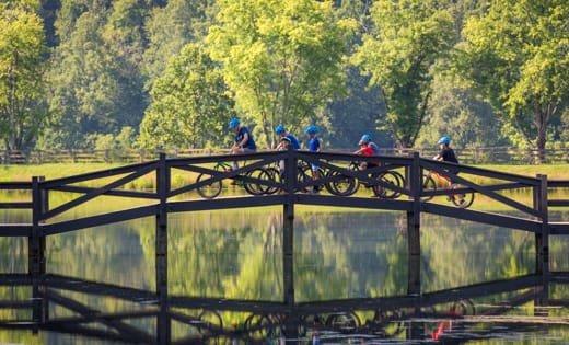 Campers biking across bridge