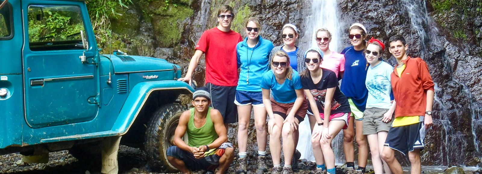 Group of teens standing by truck and waterfall