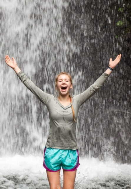Girl standing in a waterfall with arms up