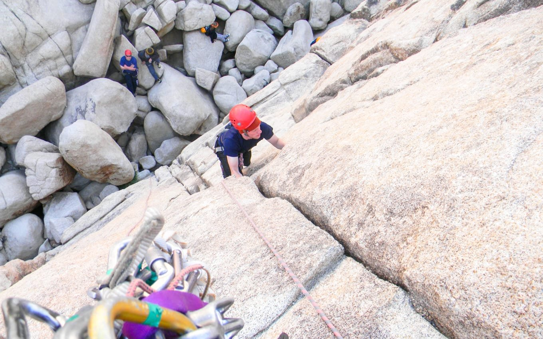 Group of teens climbing rock walls in Joshua Tree